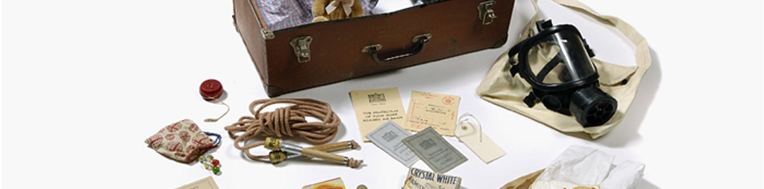 Assorted World War II objects including a gas mask, ration book, skipping rope, yo-yo. luggage label and identify card