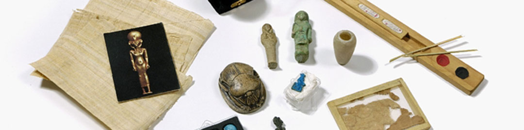 Assorted Egyptian loan box items including piece of mummy wrapping, stone figures, postcards and container of sand