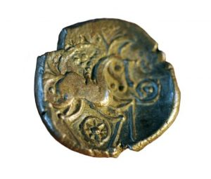 A bronze coin from the Iron Age depicting an intricate design of a horse and wheels
