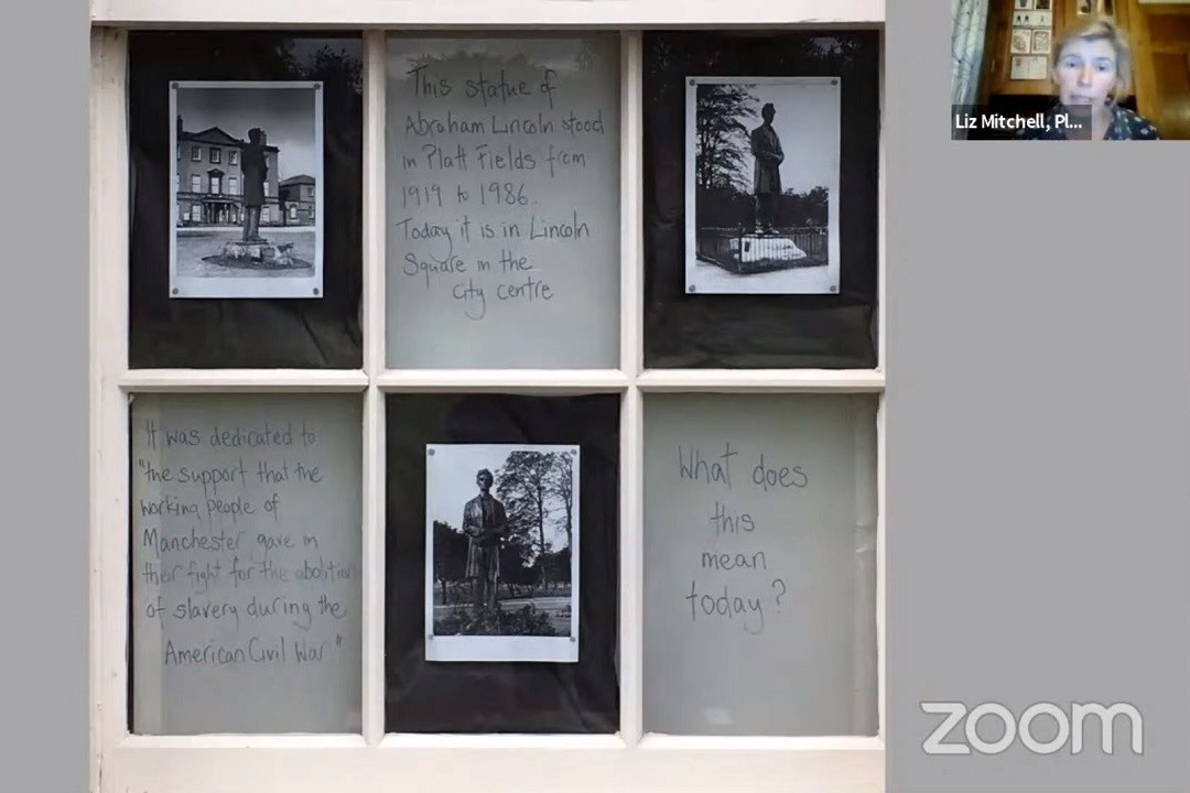 A screenshot from the Community Created Permanent Displays online seminar. The screen shows a photograph of a window. Photographs of an Abraham Lincoln statue and quotes are in each of the window panes. A white woman is talking in the top right hand corner