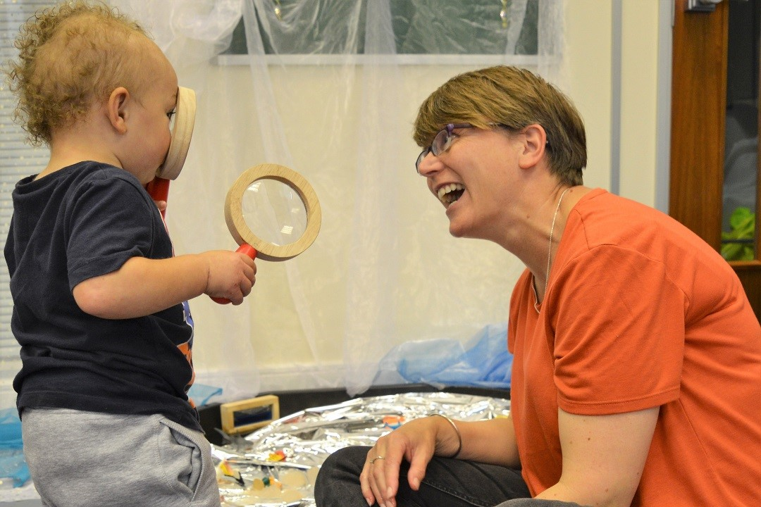 A toddler is looking through a wooden magnifying glass at a smiling adult in front of them