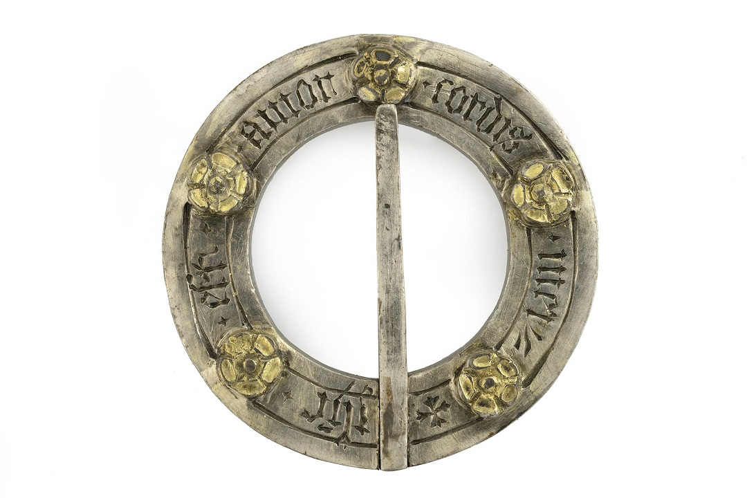 A circular silver brooch with 5 floral motifs around the edge with writing inscribed in between