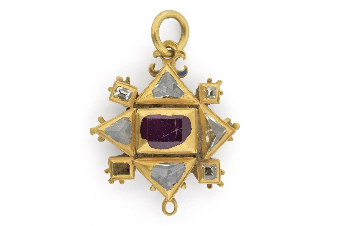 A geometric gold pendant with clear and red stones