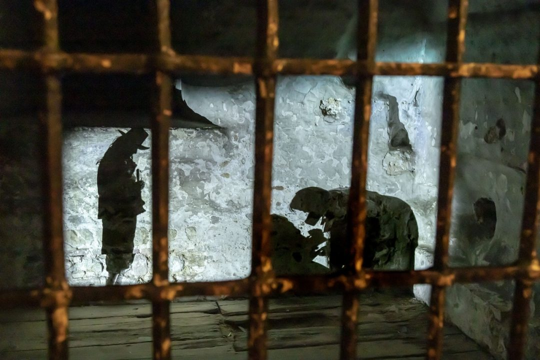 Looking through prison bars into a cell, silhouettes of people can be seen on a brick wall. One figure appears to be cowering on the ground