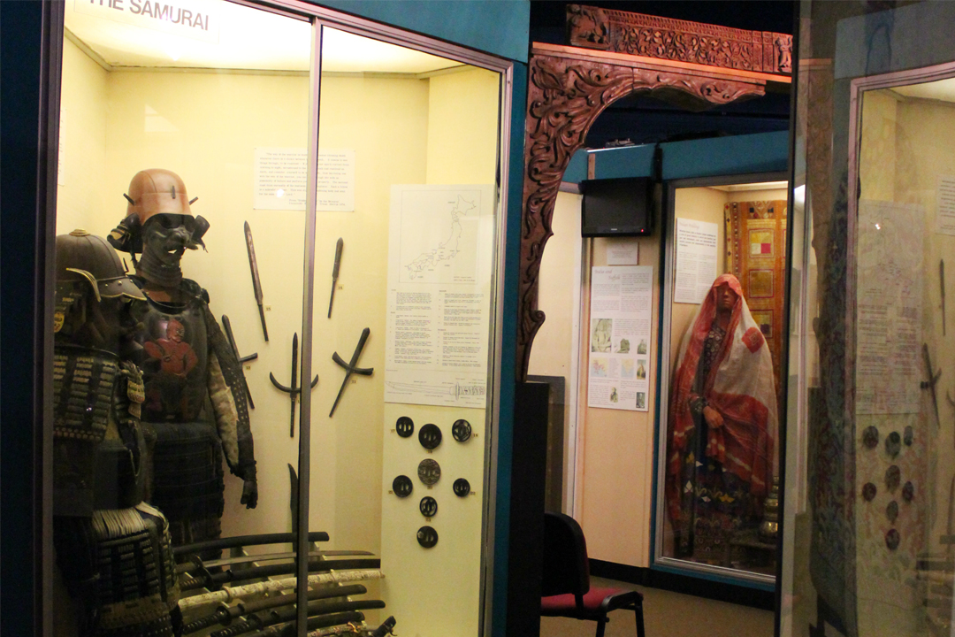 A photograph of the World Cultures Gallery at Ipswich Museum. Cases include mannequins wearing pieces of costume and weapons