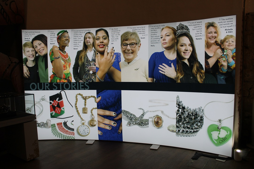 A large, curved banner. The top has photos of different people. Beneath each protrait is a close up photograph of an item of jewellery