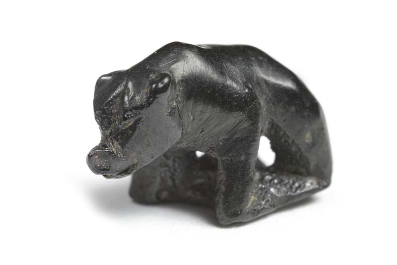 A small carved bear made from jet which is black