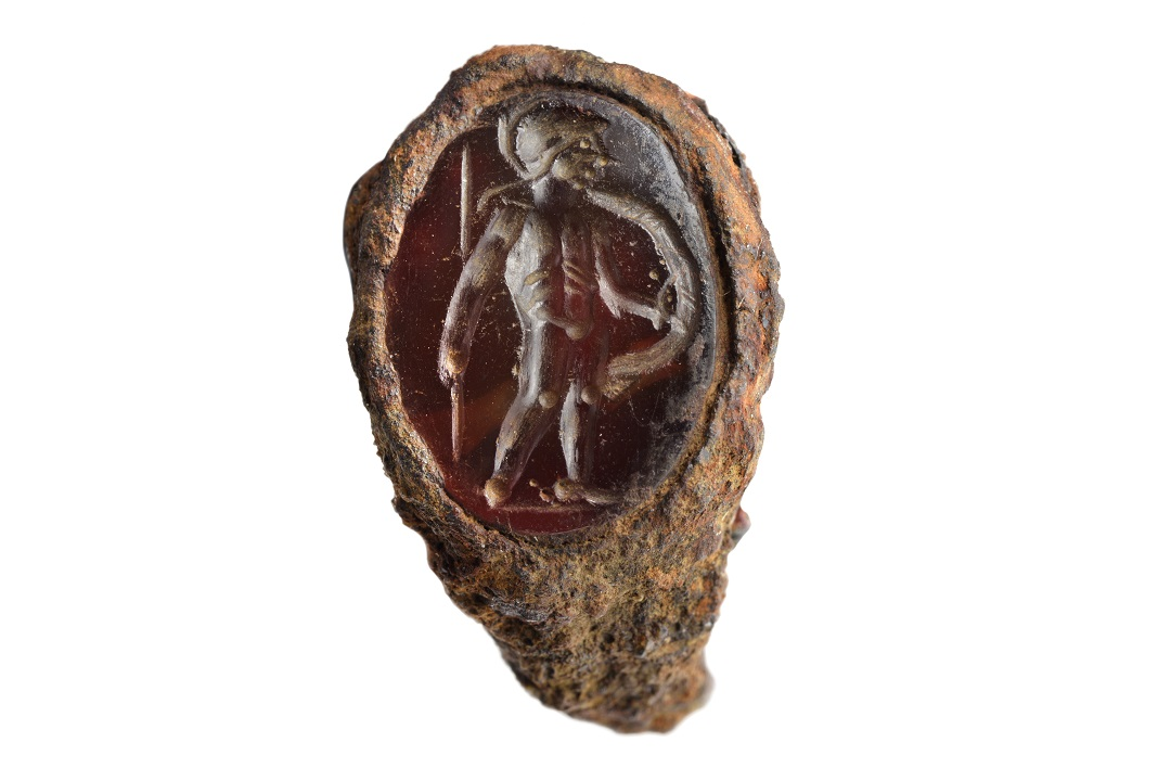 A deep red carved gem set within a aged ring. The figure carved into the gem is of a figure wearing a helmet and carrying a spear