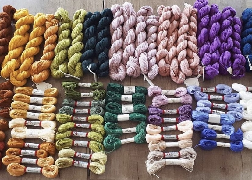 Rows of different coloured thread including shades of yellow, green, purple and cream