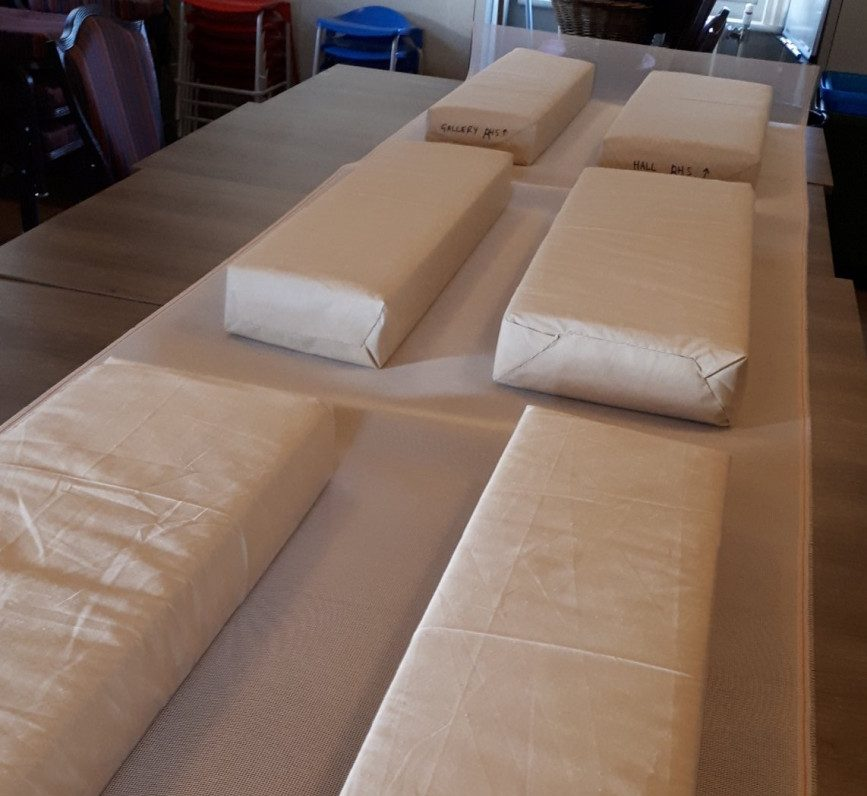 Six long rectangular cushions laid out on a table. They have been covered in a plain white fabric
