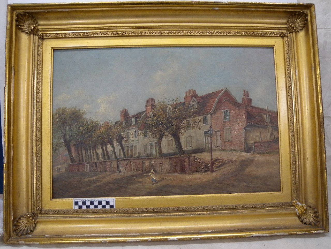 A photo of a painting surrounded by a large gold frame. The painting depicts a row of trees with a line of terrace houses behind them