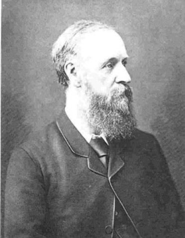 A black and white photograph of a man in a bearded man in a black suit. The photograph is of the man's face and chest. He is looking off to the right