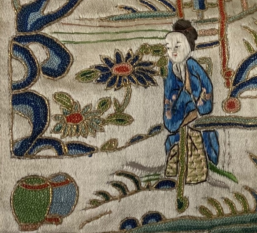 A close up of part of an embroidered panel. A Chinese figure wearing blue is surrounded by leaves and flowers