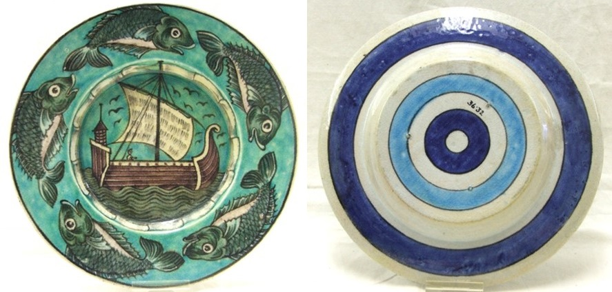 A greenish colour plate with five fish painted in a repeating pattern around the outer rim. In the centre is a large sail boat on greenish waves