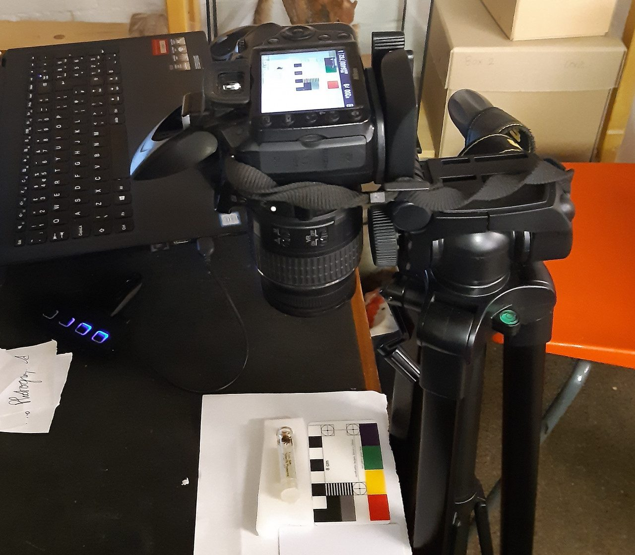 A picture of a camera set up. A DSLR camera mounted on a tripod angled with the lens facing the desk surface. Under the camera on the desk is a white piece of paper with a scale bar and colour chart and resting on a white rectangular piece of plastazote, a glass tube containing a spider and its label, which is the subject of the image being taken by the camera. A laptop keyboard and a pile of cut out labels are also on the desk; the labels all have 'Photographed' written on them.