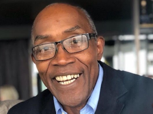 A photograph of a smiling, Black man wearing rectangular framed glasses. He has a light blue shirt and a dark blue jacket on.