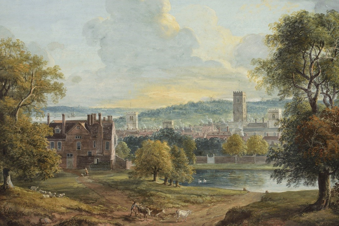 A watercolour painting showing a large, red brick building in the middle distance on the left hand side of the frame. To the right hand side is a lake, with two swans. In the immediate foreground are leafy green trees on either side and in the centre are three cows. Sheep are sat by the trees to the left. Three churches and the rooves of other buildings are visible behind a line of trees.