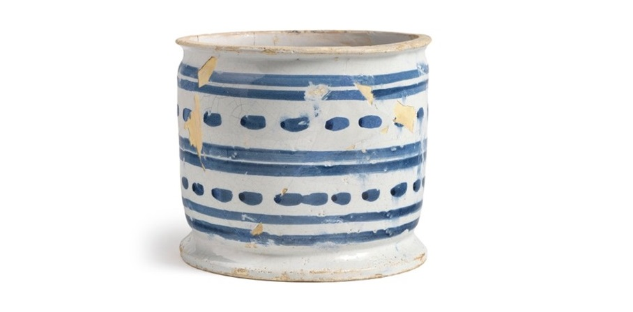 A ceramic drug jar. It is pale with a striped and dashed pattern in blue on the side. The jar is short and is open at the top
