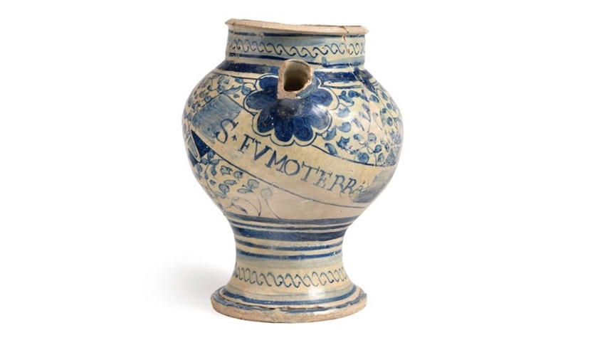 A ceramic drug jar. It is pale with ornate blue designs on the side and S FVMOTERR written in capital letters. The jar is curved, with a narrow bottom half and a rounded top half, and is open at the top