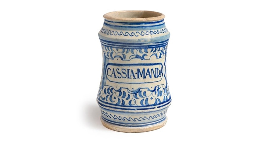 A ceramic drug jar. It is pale with ornate blue designs on the side and CASSIA MANDA written in capital letters. The sides of the jar curve inward slightly and it is open at the top