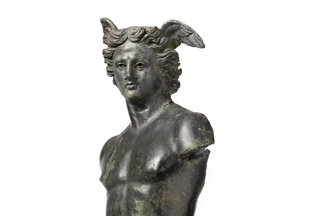 A colour photograph of the torso and head of the Colchester Mercury. It is a metal figure of a man with wings proturding from his head. The figure is missing arms