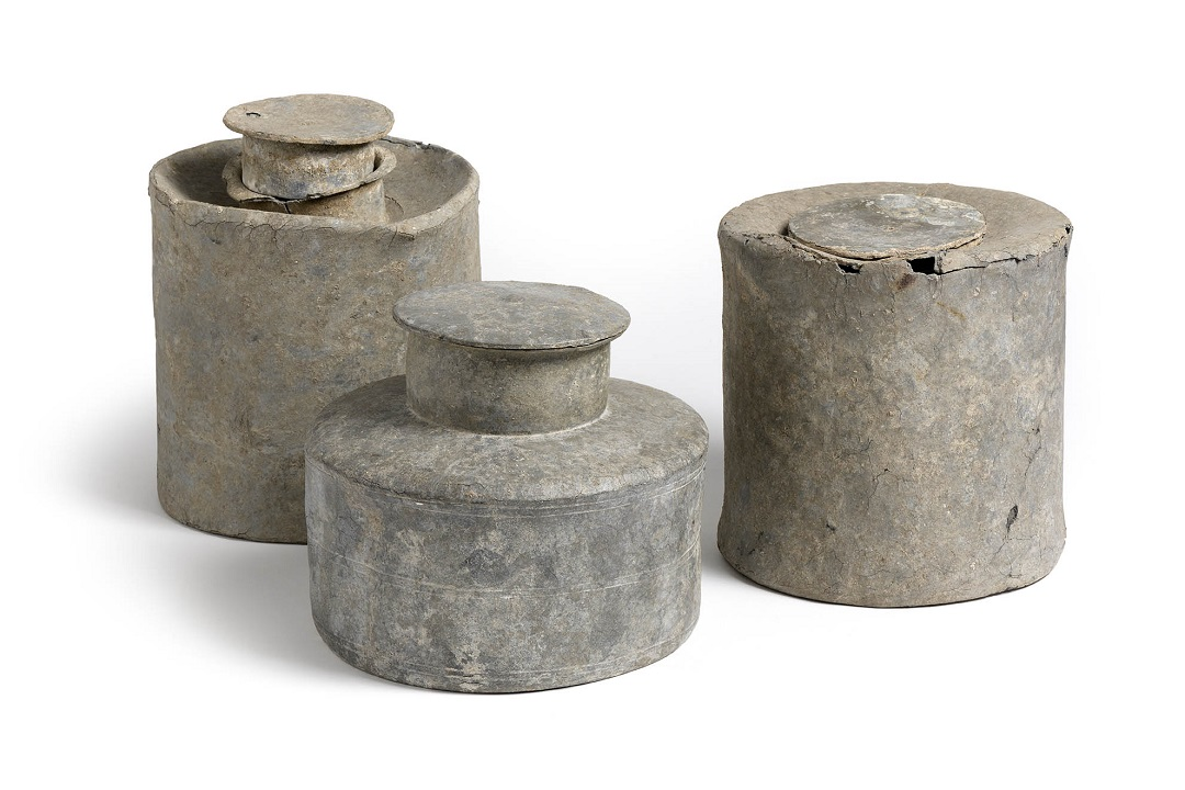 A colour photograph of three cylindrical shaped, grey coloured containers narrower neck.