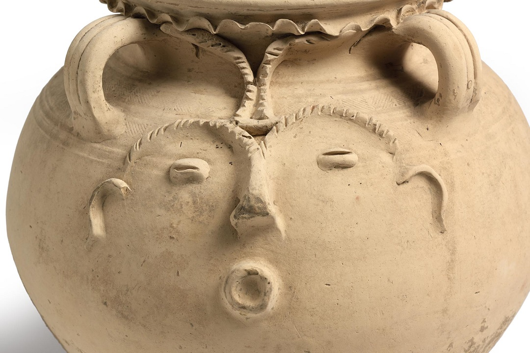 A creamy coloured ceramic pot with a face in relief on the side. The face has ears, eyebrows, a nose, eyes and a mouth pursed into an 'o' shape