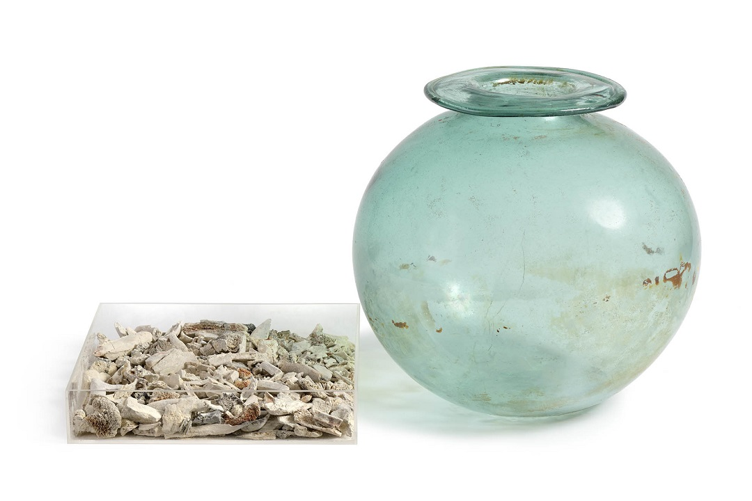 A colour photograph of a large, rounded glass vessel with a flat rim. The glass is slightly greenish in colour. To the left of the vessel is a shallow, square shaped clear container full of bone fragments