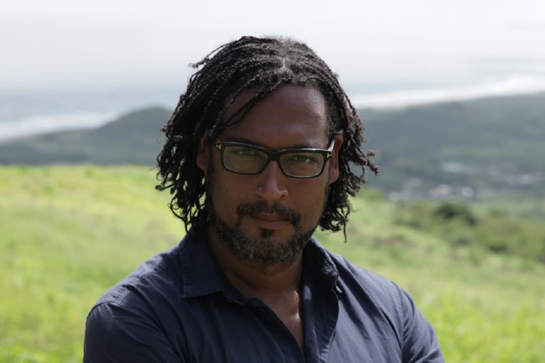 A colour head and shoulder photograph of a black man wearing rectangular framed black glasses and a dark blue shirt. He has hair in fine braids and is looking at the camera. Behind the man is a grassy landscape which is out of focus.