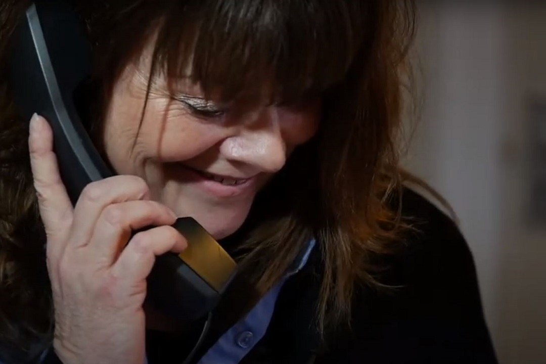 A colour photograph showing a member of the Ipswich Museums Visitor Services team. The photograph is of a smiling white woman white wavy brown hair on the phone.