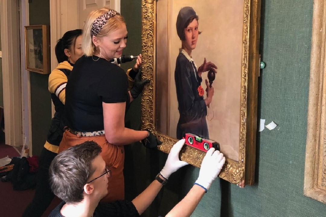 A colour photograph showing staff hanging a painting in Christchurch Mansion. A man is knelt in the foreground hold a spirit level against the frame, a woman is holding the picture level while a third person in the background is attaching the painting to the wall with an electric screwdriver