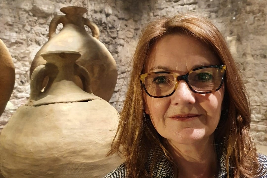 A colour photograph of a white woman with should length brown hair and glasses. She is stood inside Colchester Castle, in front of a display case containing large ceramic vessels