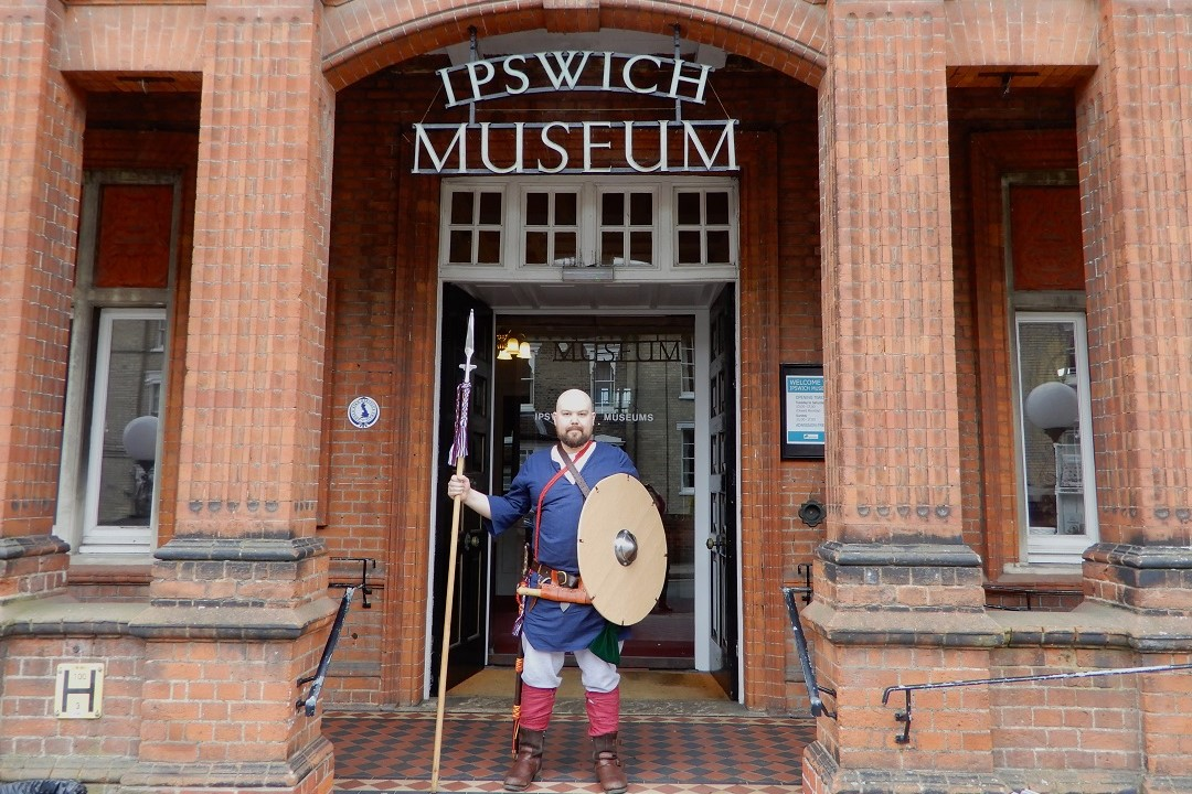 A colour photograph showing a white man wearing a Saxon costume stood outside the entrance to Ipswich Museum. The man is wearing a dark blue tunic with a belt around the waist and brown boots. He is holding a large round shield and long spear.