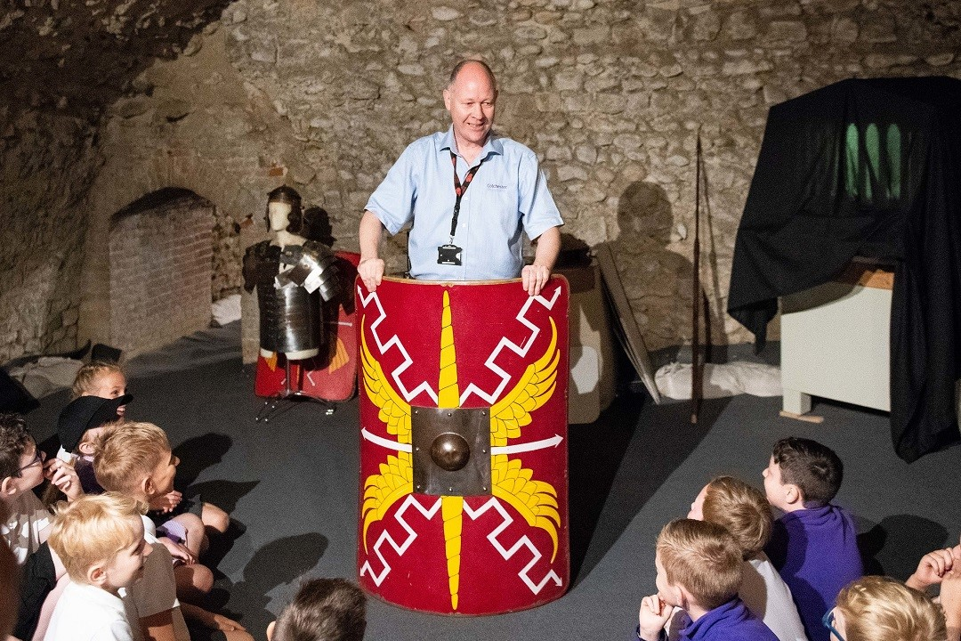 A colour photograph showing a white man in museum uniform stood behind a large replica Roman sheild. The shield is rectangular and covered in a red, yellow and white design. In front of the man are school children sat on the floor